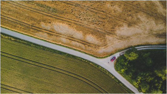 Aerial overhead view of a car driving through farmland